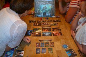 Bild: drei Spieler, am Tisch sitzend mit aufgedeckten Spielekarten