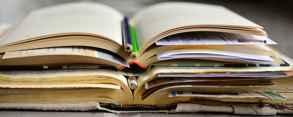 Aufgeschlagene Bücher, übereinander gestapelt