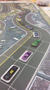Bild: Spielfeld Rennbahn mit Autos auf Kärtchen abgebildet
