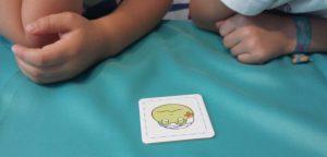 Bild: Kinderhände mit 1 Karte mit Froschgesicht