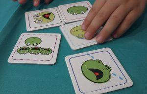 Bild: 5 Karten mit Froschgesichtern sowie eine Kinderhand