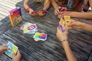 Bild: Spieler am Tisch sitzend mit Spielkarten in den Händen