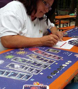 Bild: Spielefeld mit Karten sowie eine Frau, die Spielergebnisse auf Block notiert