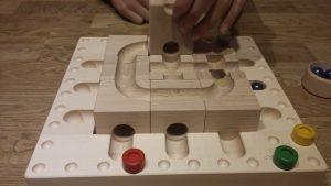Bild: Holzbahn mit Murmeln und Spielsteinen