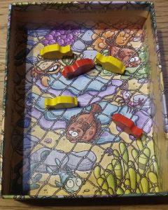 Bild: geöffnete Spielschachtel mit Fischernetz und Holzfischen