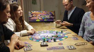 Bild: Spielergruppe um das Spielmaterial am Tisch sitzend
