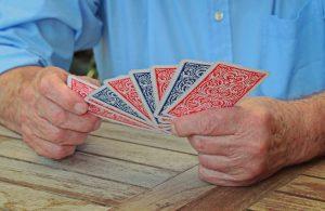 Bild: Mann hält Spielkarten in seinen Händen