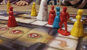 Bild: einzelne Spielfiguren in Menschengestalt und Figur Schlossgespenst, auf Spielfeldern stehend