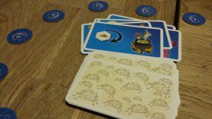 Bild: verdeckte und auftgedeckte Aktionskarten und Spielchips