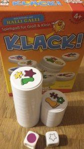 Bild: im Hintergrund Spielschachtel Klack, im Vordergrund gestapelte Spielscheiben und Würfel