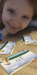 Bild: Mädchen mit Spielkarten, auf denen Zahlen aufgedruckt sind