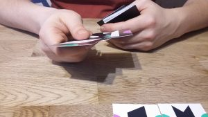 Bild: ein Spieler hält Spielkärtchen in seinen Händen
