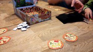 Bild: geöffnete Spielschachtel und Spielmaterial auf Tisch