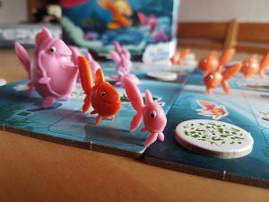 Bild: Spielfeld-Ausschnitt mit Spielfiguren Fische und Spielplättchen