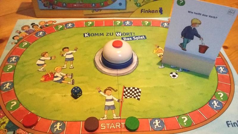 Bild: Spielfeld mit Buzzer, Spielsteinen und Spielkärtchen