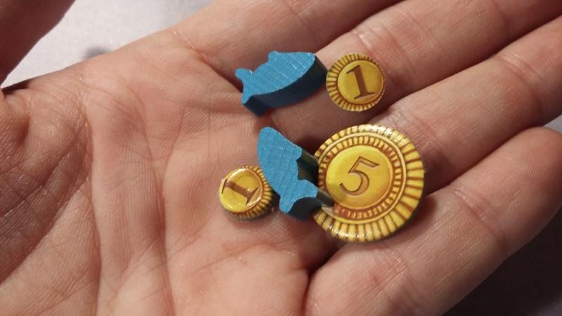 Bild: auf einer Spielerhand liegen kleine Spielsteine und Spielmünzen (Karton)