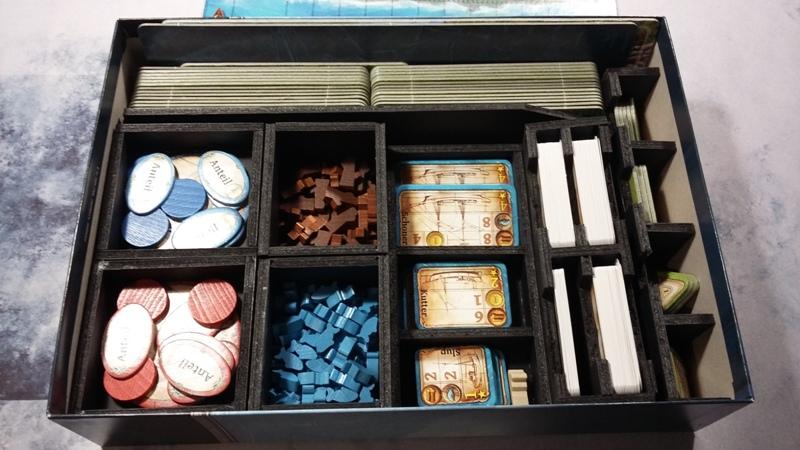 Bild: Spielschachtelinhalt mit Kärtchen, Spielsteinen und Spielplättchen