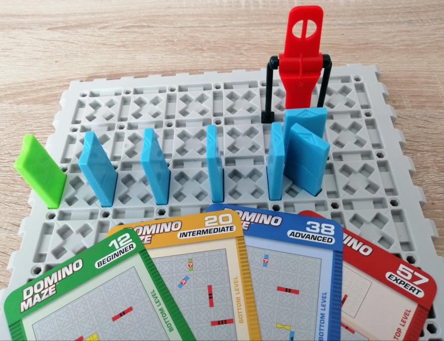 Spielbrett mit Dominosteinen und Beispiele der vier Schwierigkeitsstufen.