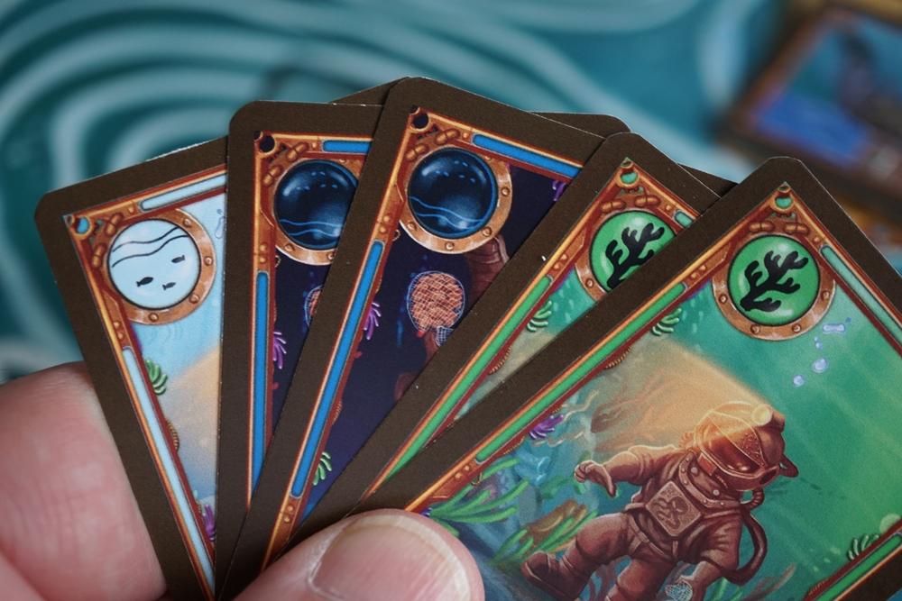 Hand mit unterschiedlichen Karten, die sich durch Farben und Symbole unterscheiden