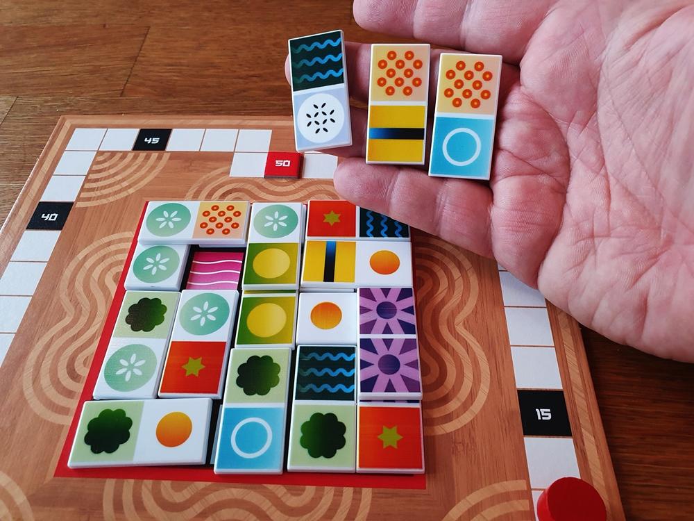 Eine Hand mit drei Spielsteinen über einem halb gefüllten Spielbrett