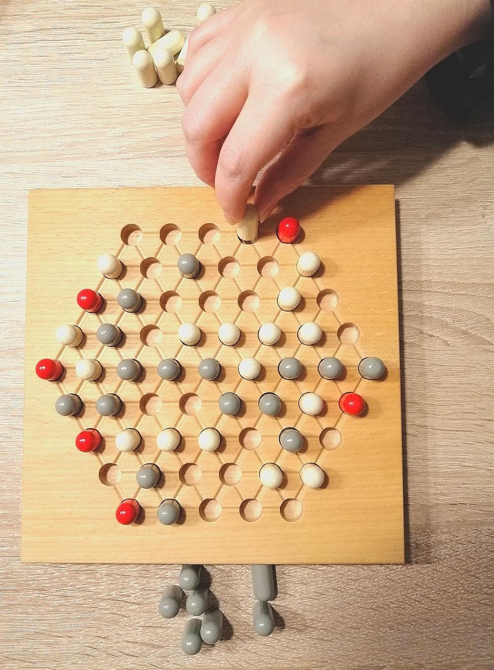 Ein Spielstein wird gesteckt.