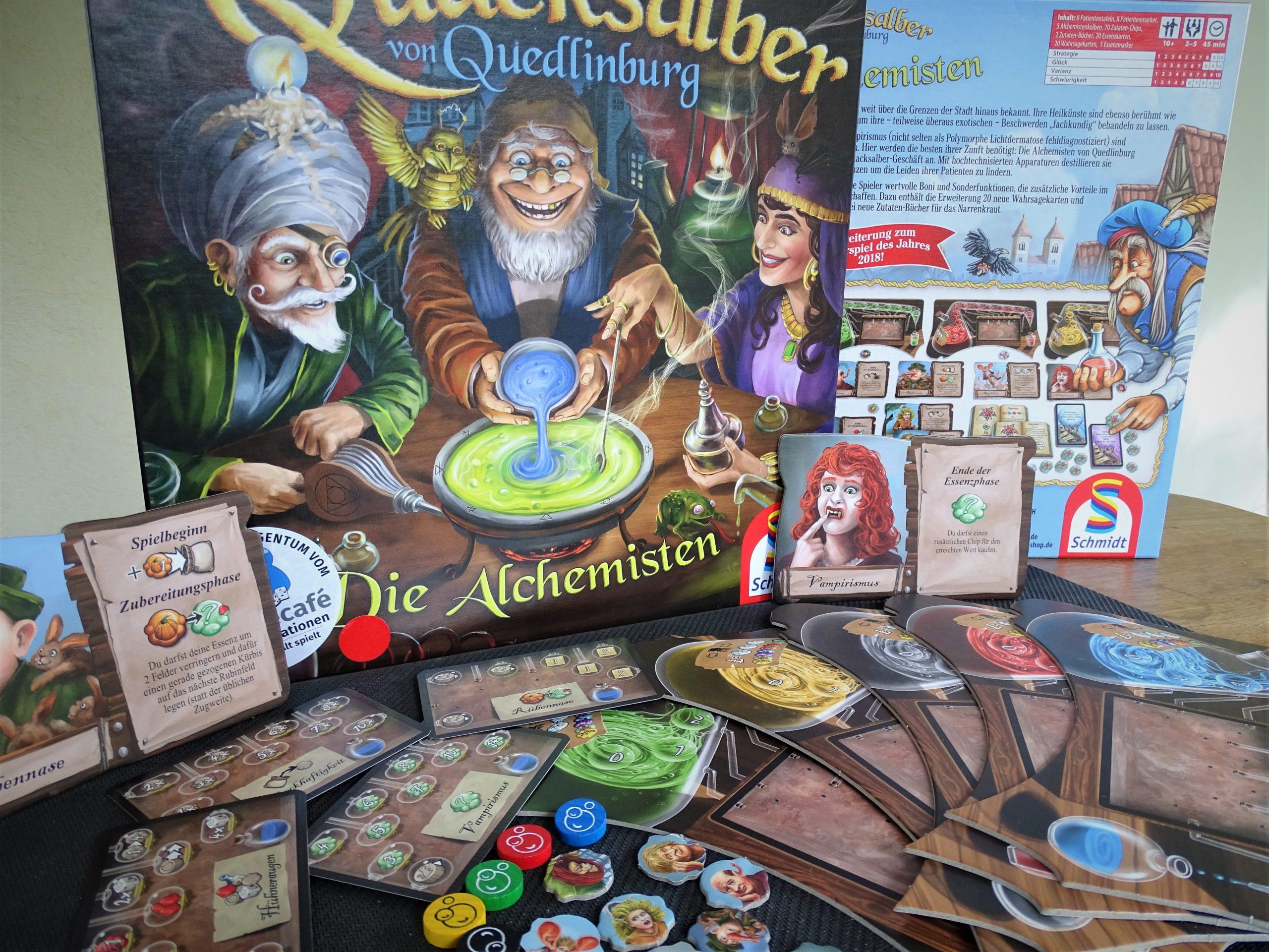 Blick auf die Kartonvorderseite, Rückseite und den neuen Inhalt der Alchemisten