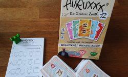 Spielkarton, enthaltene Spielkarten, grüne Figur und Wertungsblock