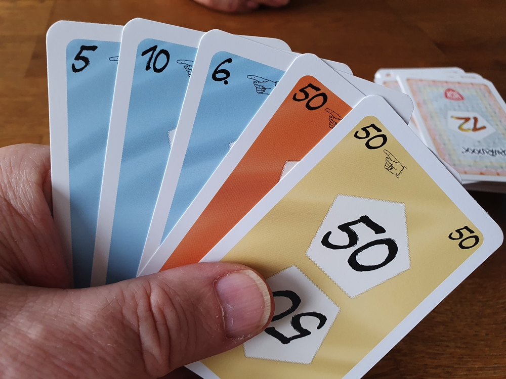 Kartenhand mit zwei Karten im Wert 50 in unterschiedlichen Farben