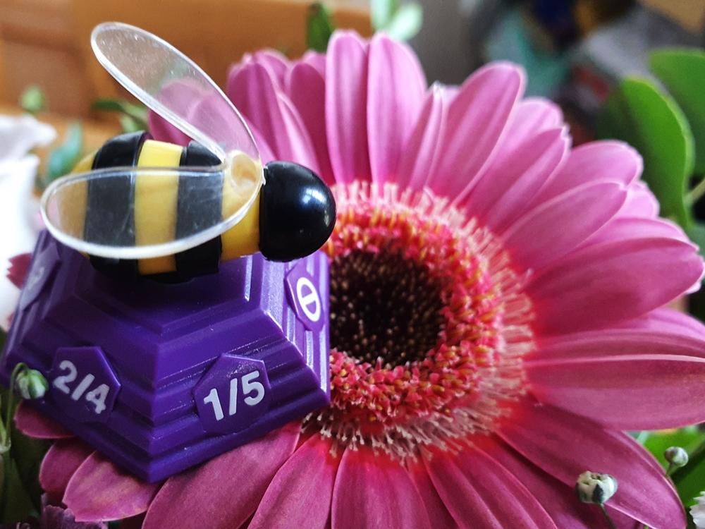 Spielfigur Biene auf echter Blüte