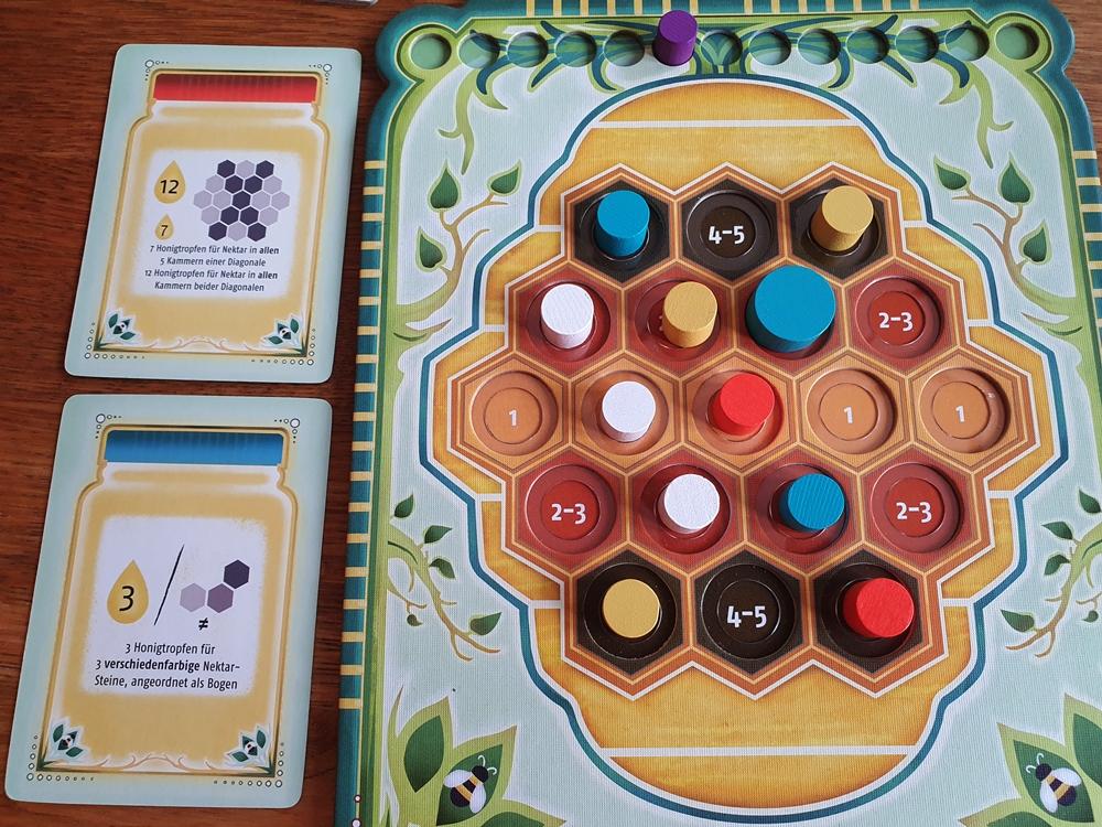 Spielbrett eines einzelnen Spielers, einer Spielerin. Wabenfeld mit Nektarsteinchen weitgehend gefüllt. Daneben persönliche Aufgabenkarten