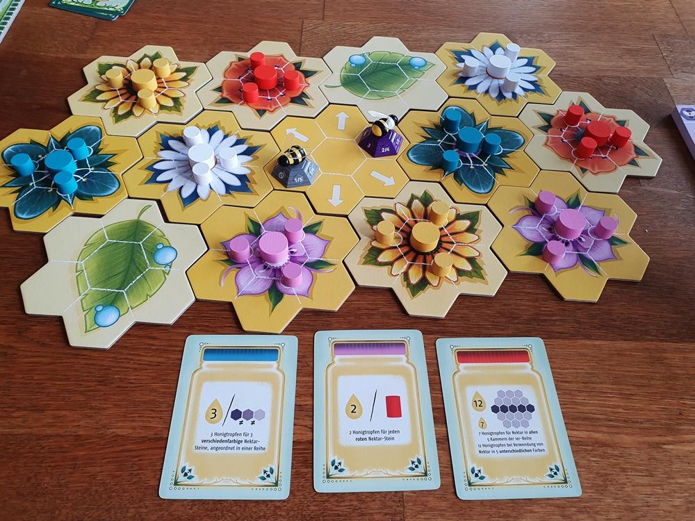 Aufgebauter Spielplan aus Blütenplättchen, darauf Spielsteine und davor Aufgabenkarten
