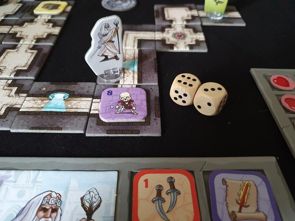 Spielfigur steht in einem Höhlenraum. Gegner hat die Stärke 8. Zwei Würfel mit der Summe 9