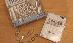 """Zu sehen sind die Verpackung des Spiels """"Trilos"""" sowie der Aufgabenblock und die 5 Zahnrad-Aufleger unterschiedlicher Formen."""