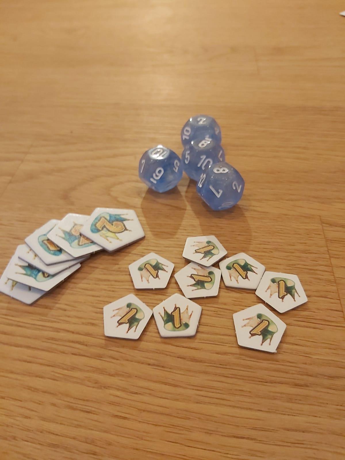 Zu sehen sind die Würfel und Siegpunktmarker des Spiels