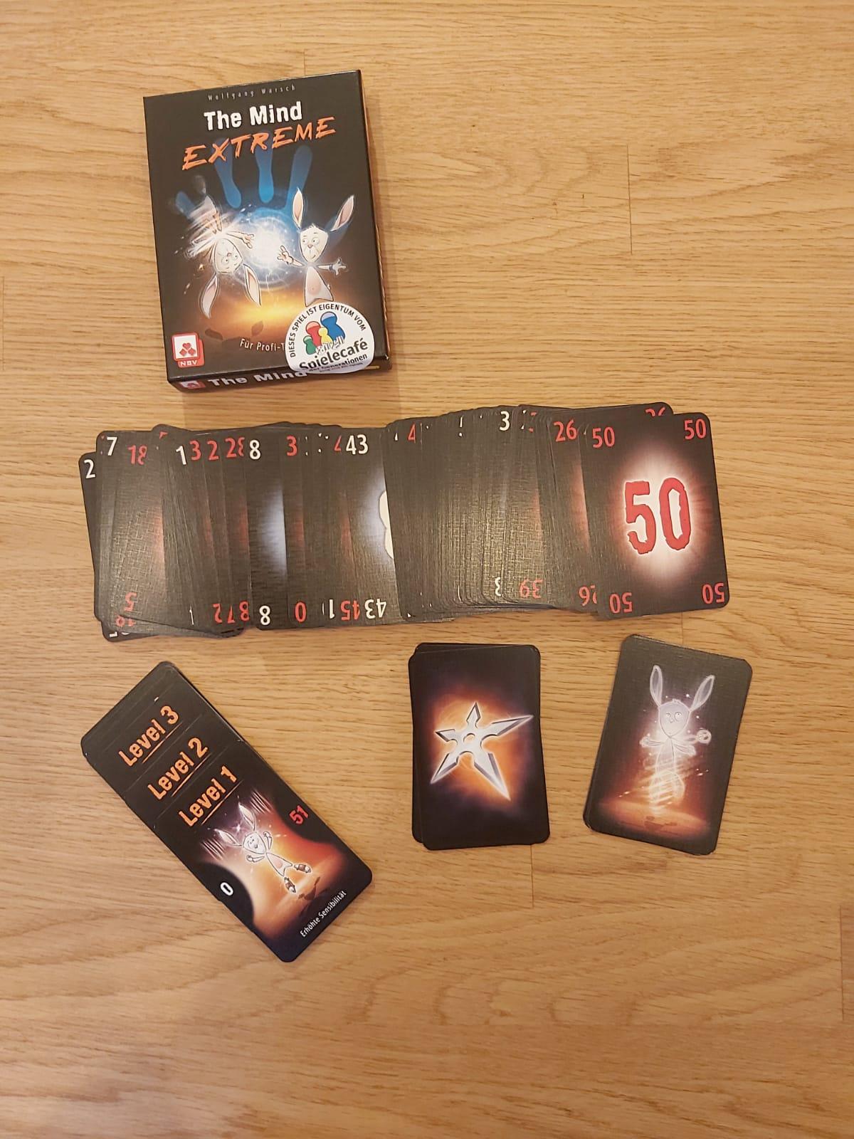 Zu sehen sind die Verpackung von The Mind Extreme sowie alle zum Spiel gehörenden Spielkarten.