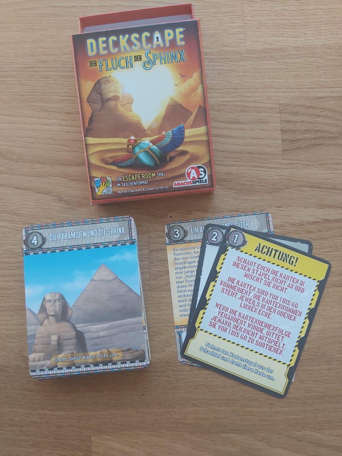 Zu sehen ist Deckscape Fluch der Sphinx samt Spielmaterial