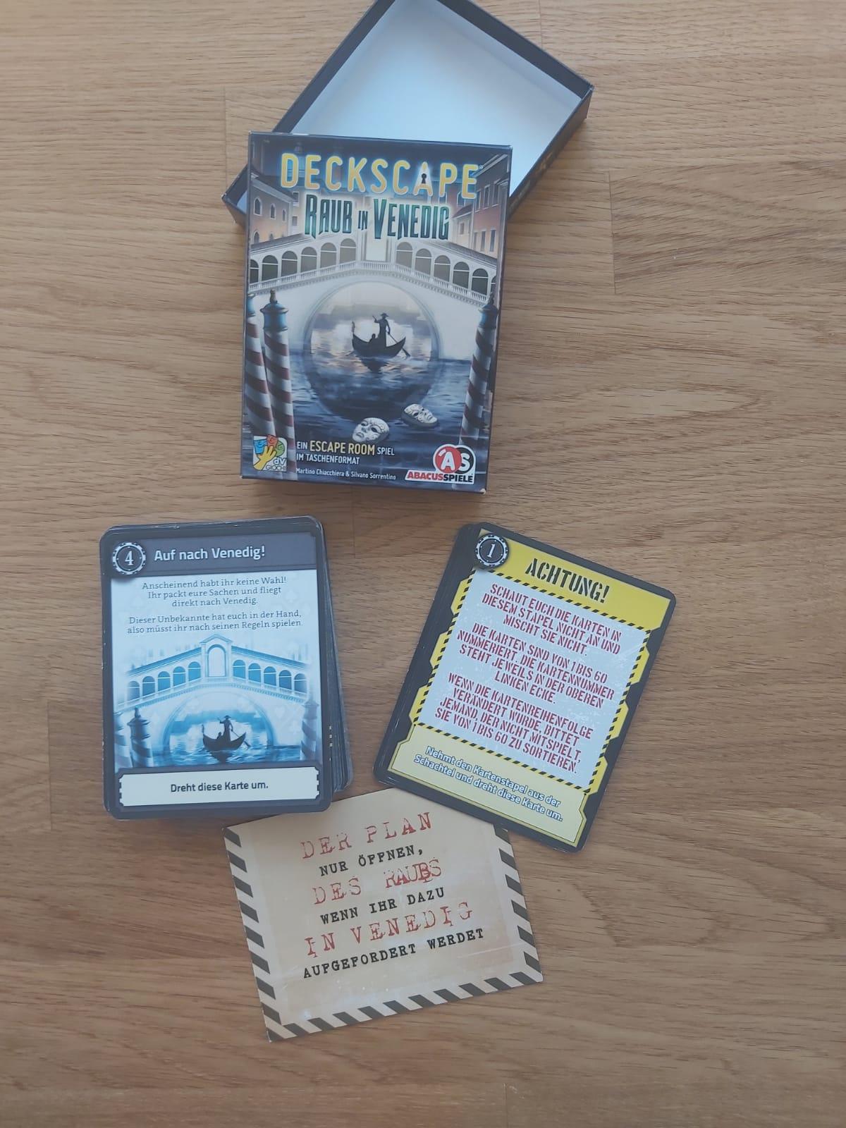 Zu sehen ist Deckscape - Raub in Venedig samt Spielmaterial