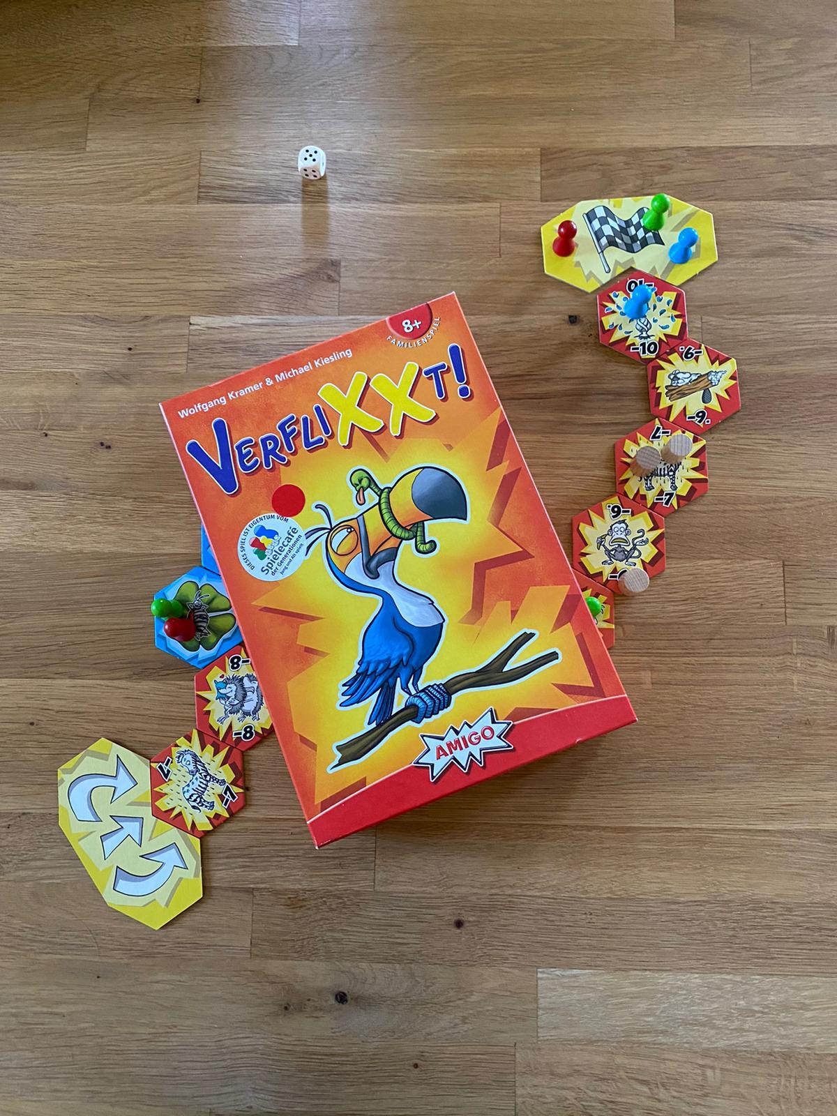 Zu sehen ist das Spielmaterial von Verflixxt sowie die Verpackung