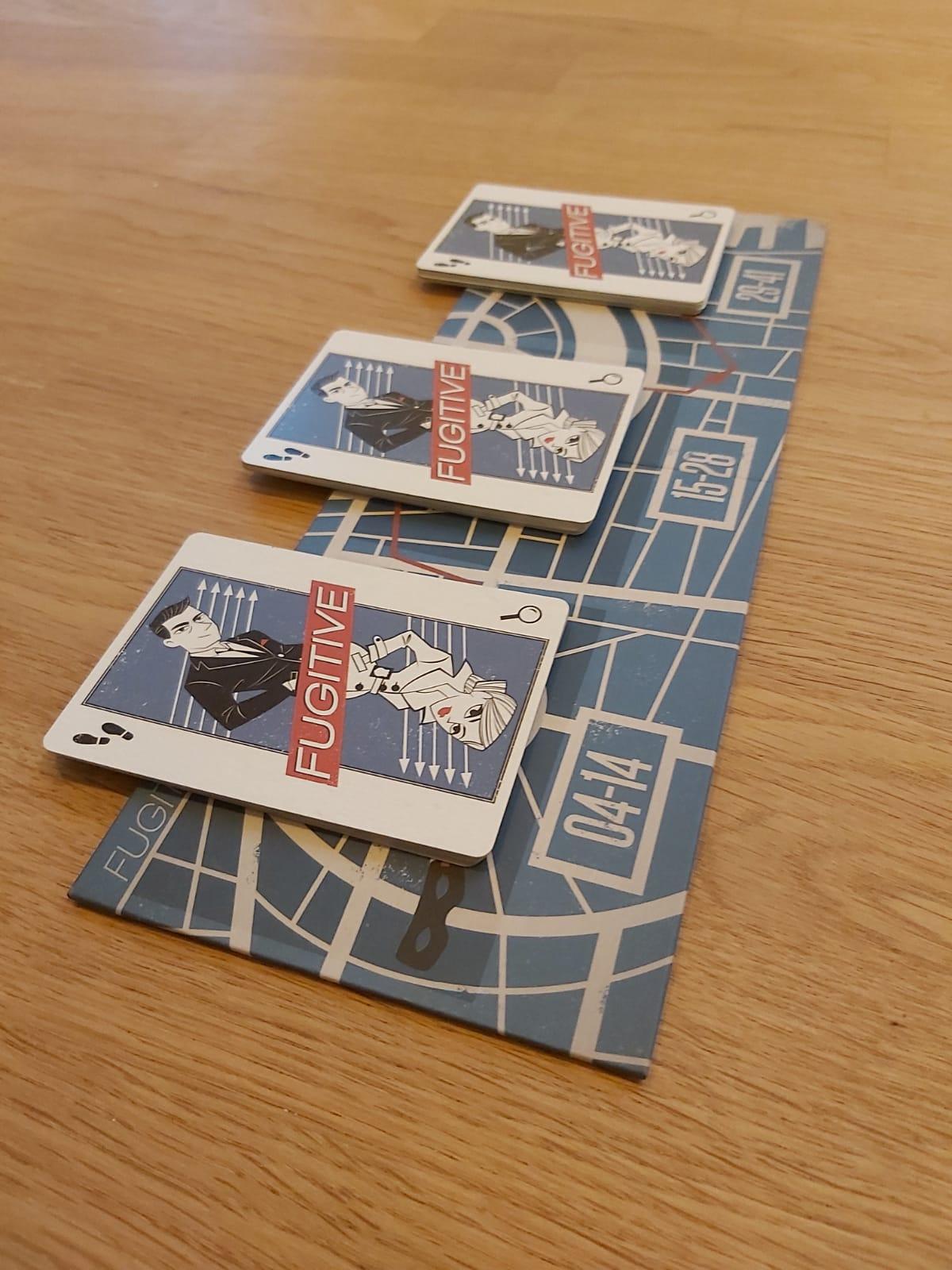 Zu sehen sind die 3 Kartenstapel von Fugitive, die am Spielanfang präpariert werden.