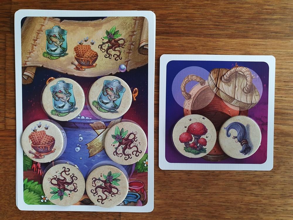 Erfüllte Zaubertrankarte mit Zutatenplättchen belegt, die Müllkarte ist teils belegt