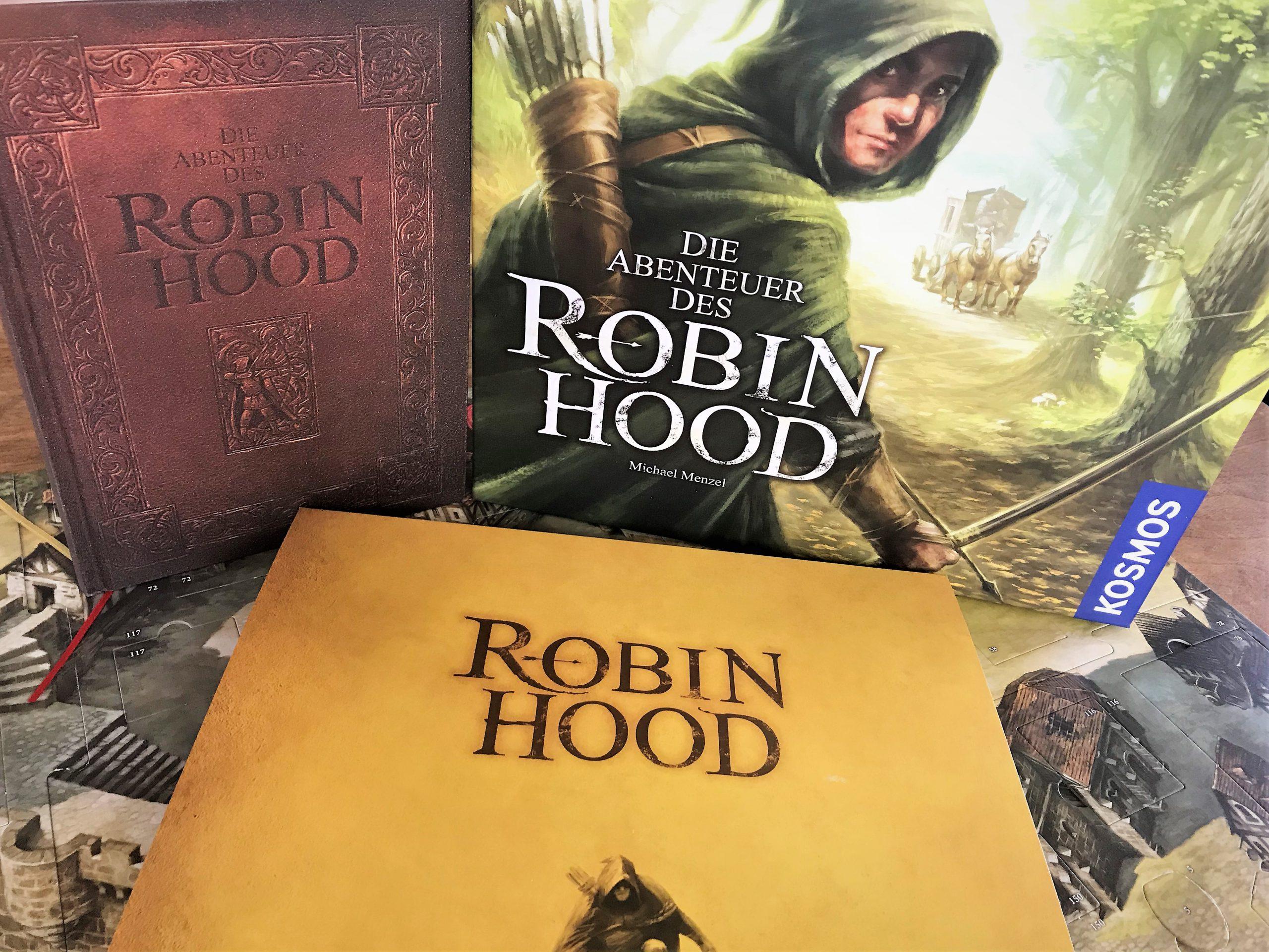 EIn Block auf die Schachtel, das Abenteuerbuch und den Schuber des Spielplans.