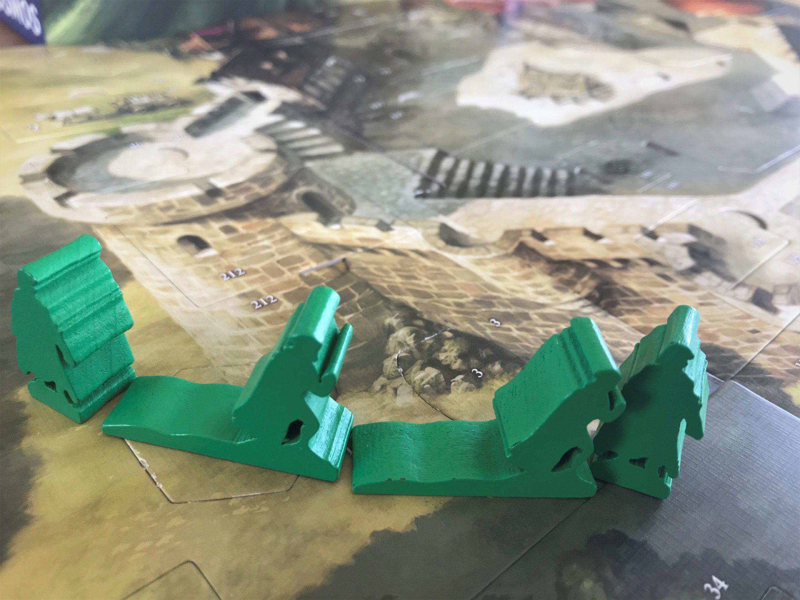 Mit Holzfiguren bewegen sich die Held:innen über den Spielplan