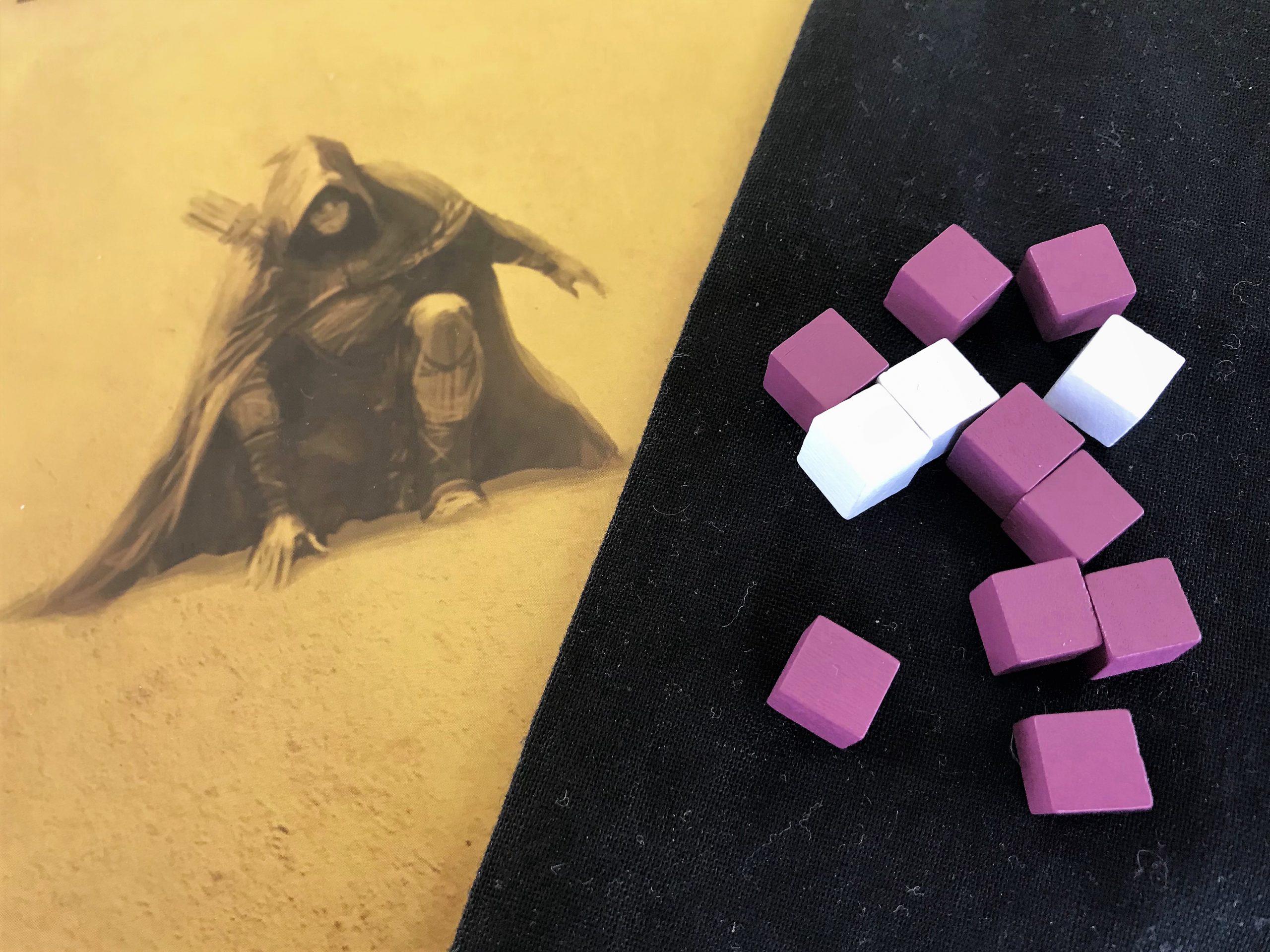 violette und weiße Würfelchen kommen in einen Stoffbeutel
