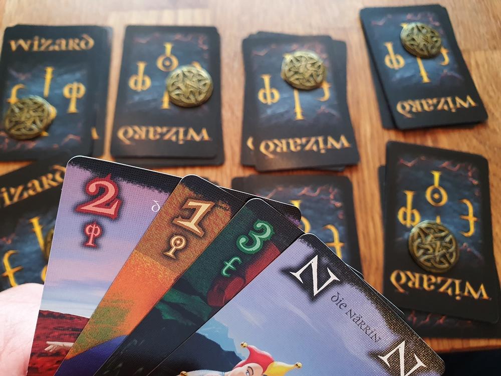 Hand mit vier Restkarten, abgelegte Stiche mit jeweils einer Münze darauf.