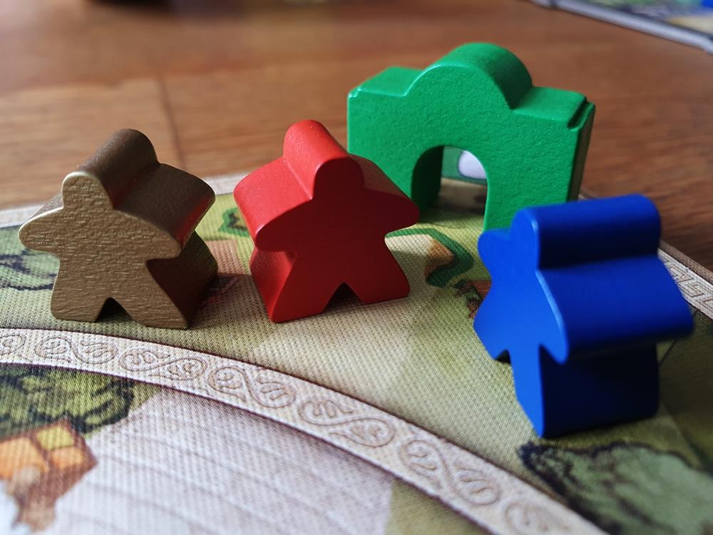 Grünes Tor in einem Eck des Spielplans, dazu mehrere Meeple
