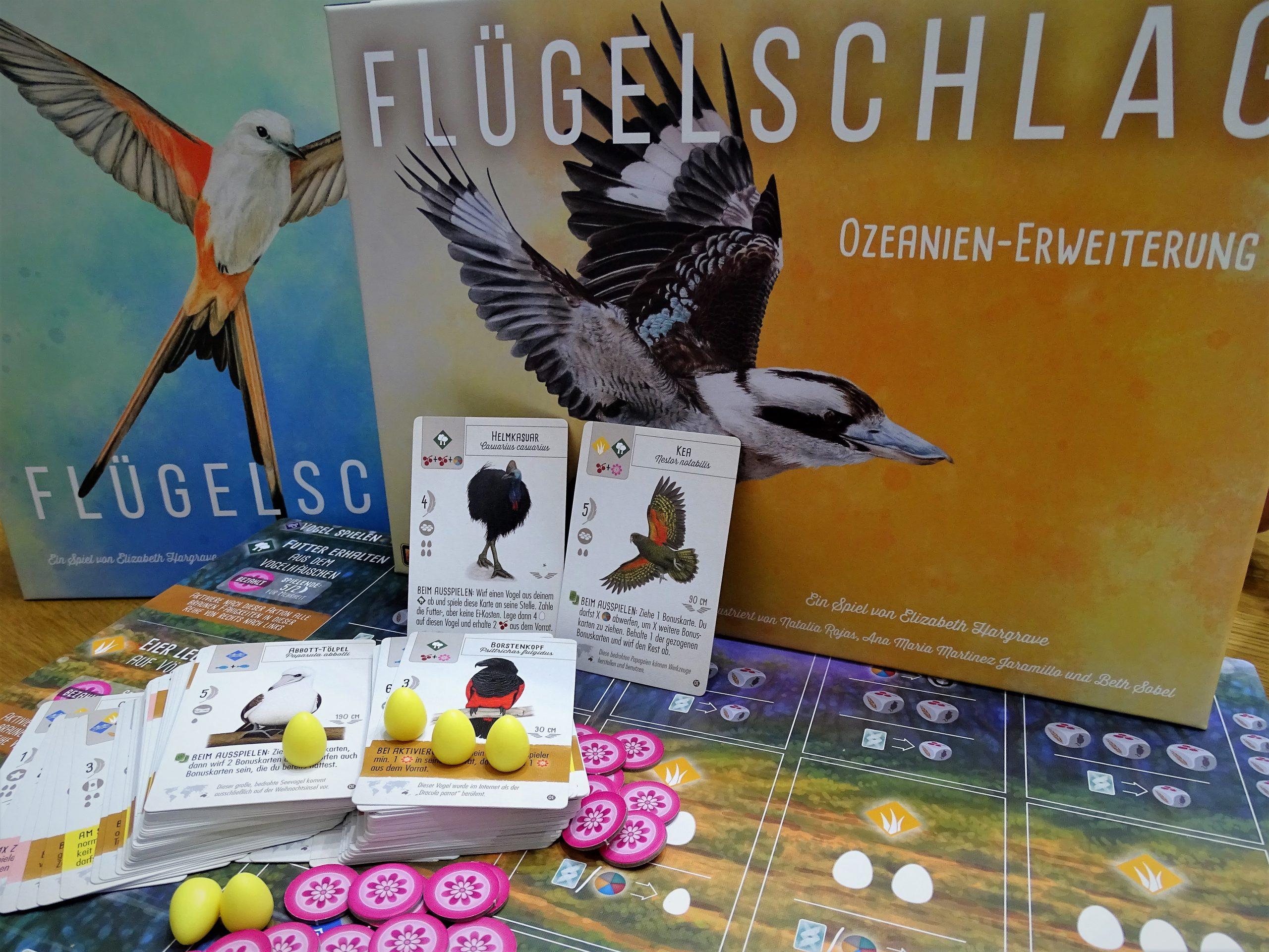Die Schachteln der Erweiterung und des Grundspiels mit einem Blick auf die neuen Vogelkarten und das Tableau