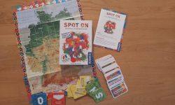 Zu sehen ist die Verpackung samt Spielmaterial von Spot on.
