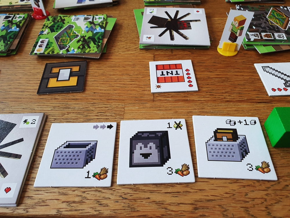Spielsituation. Vor dem Spielenden liegen drei erworbene Gegenstände