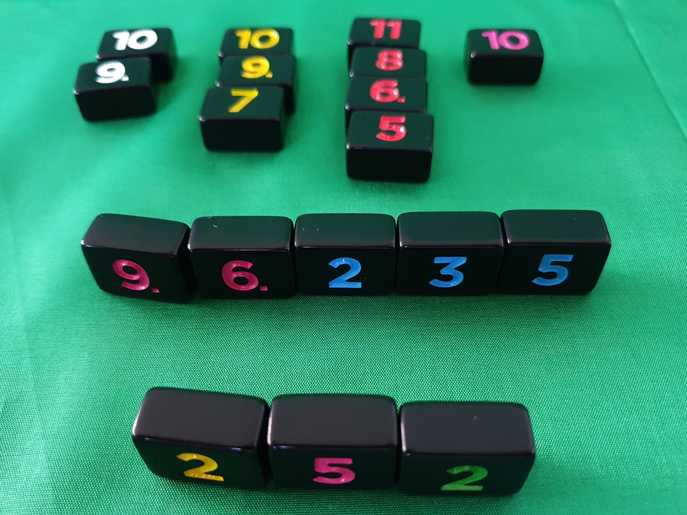 Acht aufgestellte Steine eines Spielenden, dahinter Auslage von Steinen in vier Farben