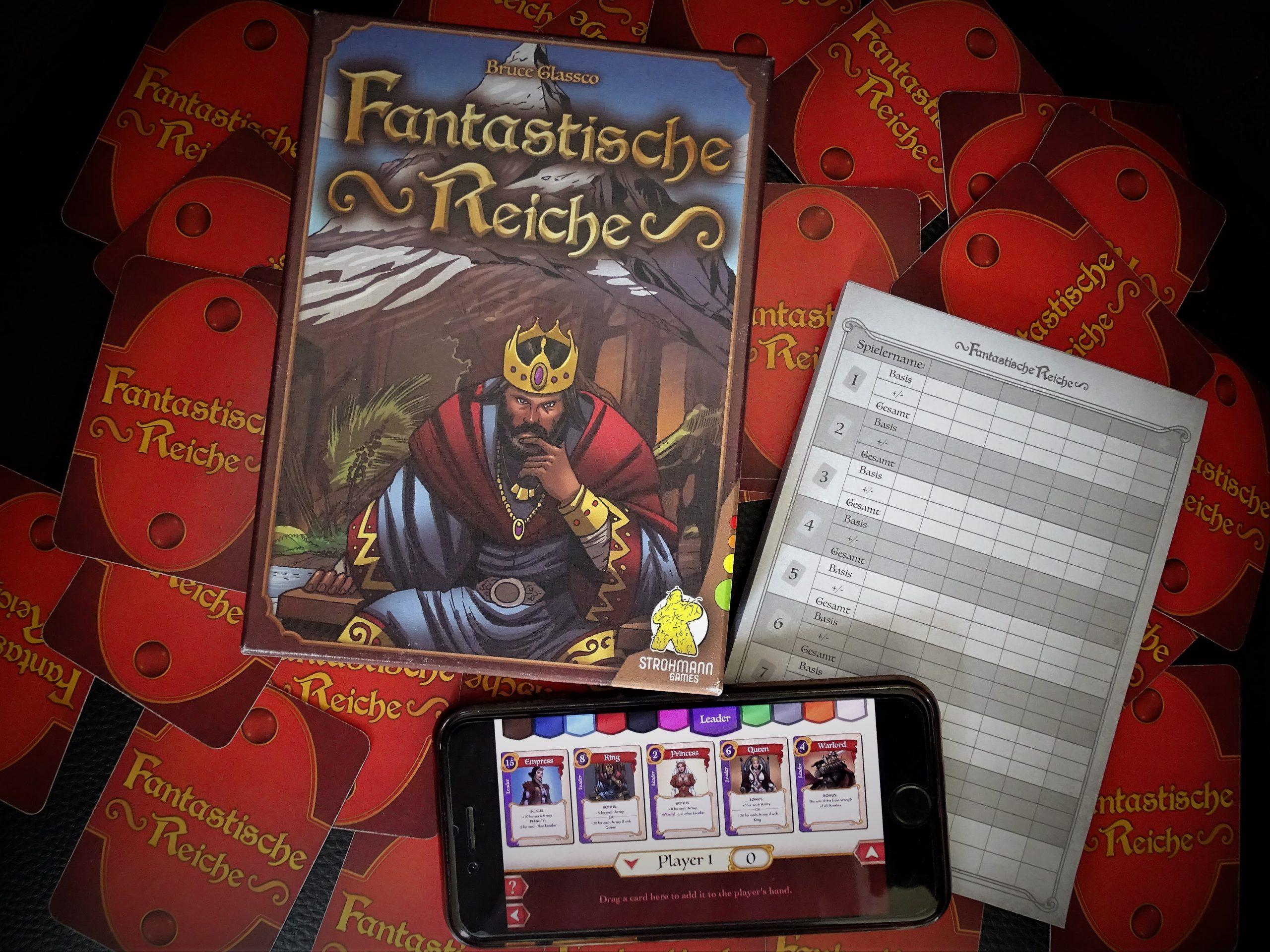 Die Schachtel des Spiels liegt auf den umgedrehten Karten, daneben ein analoger und ein digitaler Wertungsbogen